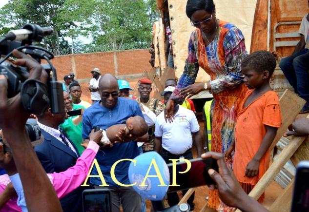 Mme Virginie Mbaïkoua remettant un bébé né parmi les réfugiés de Bétou à M. Raouf Mazou à leur arrivée à Moungouba