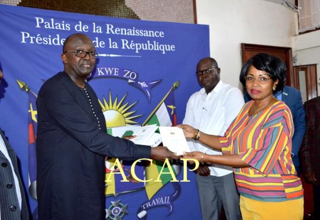 Mme Léonie Banga-Boti recevant des mains de Freddy Nkurikiyéquelques copies de l'Accord de paix et de réconciliation