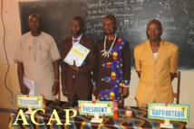 Le capitaine des FACA, tenant son mémoire de soutenance,entouré de l'assesseur,du président et du rapporteur