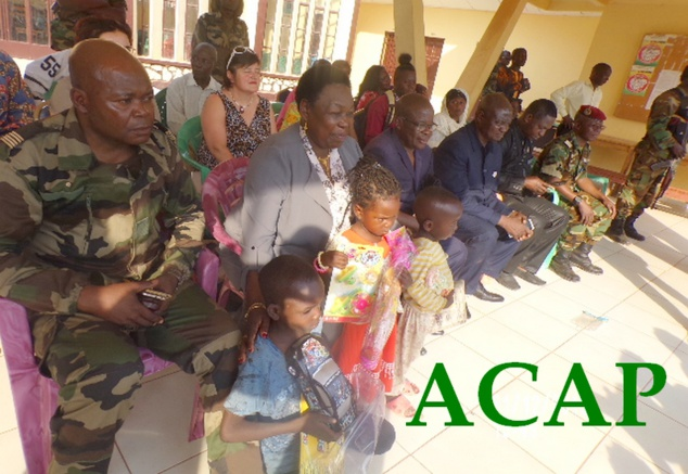 Madame M.N KOYARA tenant chaleureusement des enfants après réception de leur jouets