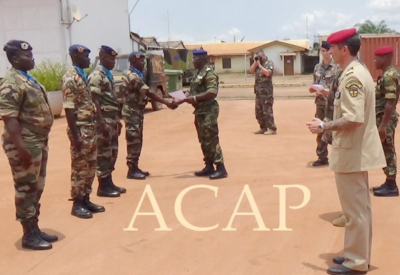 le chef de corps de l'armée de l'air remettant une attestation à un récipiendaire en présence des militaires français