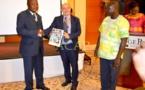 Le représentant du ministre de l'Economie (g) remettant un exemplaire du rapport à un officiel